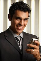Hispanic businessman holding cell phone