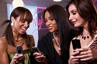 Multi-ethnic women looking at cell phones