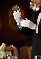 Hispanic male waiter examining wine glass
