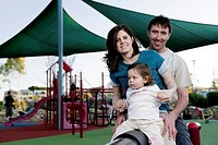 Parents and daughter playing in the playground