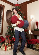 Hispanic couple playing next to Christmas tree