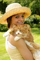 Teenage girl with hat hugging her pet cat