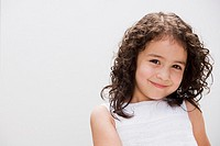 Studio shot of young Hispanic girl smiling