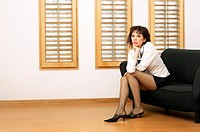 Sexy businesswoman sitting on the couch