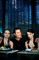Man posing with two women in a luxurious restaurant