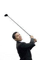 Businessman swinging golf club