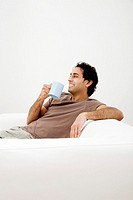 Man sitting on the couch drinking coffee