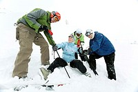 Male skiers helping a female skier to stand up