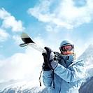 Woman in ski goggles holding snowboard