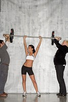Female athlete lifting weights with help