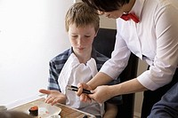 Food server showing boy how to use chopsticks