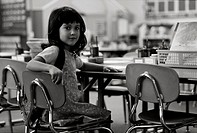 Young girl sitting at school table