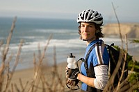 Female cyclist stopping near coast, California