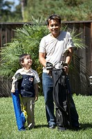 Young boy and his father carrying golf bags