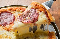 A slice of salami pizza being lifted up on server (thumbnail)