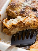 Lasagne in baking dish with spatula