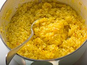 Saffron risotto in pan with spoon