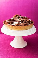 Whole chocolate tart on cake stand