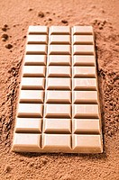 A bar of milk chocolate on cocoa powder