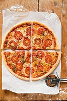 Cheese and tomato pizza with oregano quartered
