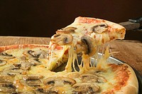 American-style mushroom pizza with piece on server