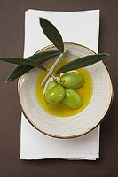 Green olives on twig in bowl of olive oil overhead view