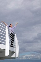 Businesswoman with arms raised on balcony