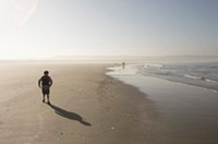 Young boy walking on beach