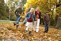Family kicking autumn leaves in park