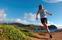 Young woman running along remote coastline, Hawaii