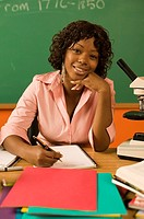 African teacher sitting at her desk