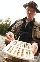 Senior fisherman with fly-fishing flies