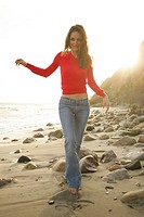 Woman walking on rocky beach