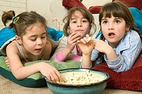 Young girls eating popcorn at a sleepover