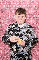 Dressed up young boy eating pear