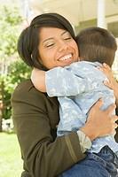 Hispanic military soldier hugging her son