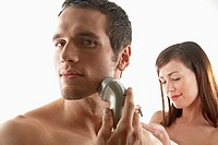 Young man shaving his face with woman in background