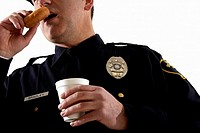 Male police officer having coffee and a doughnut