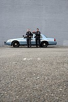Male police officers standing by patrol car
