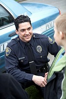 Male police officer talking to a young boy