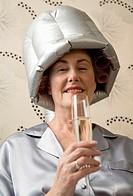 Senior woman enjoying champagne underneath hair dryer