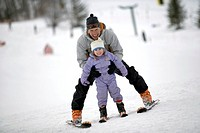 Father skiing with daughter