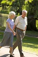 Senior couple holding hands walking