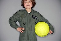 Young boy in jumpsuit holding ball