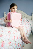 Young girl holding suitcase on bed