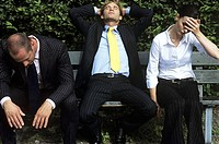 Frustrated business people sitting on bench