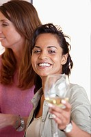 Woman of Indian ethnicity drinking white wine