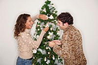 Couple decorating Christmas tree (thumbnail)