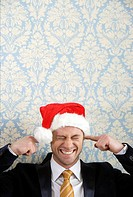 Smiling man in Santa hat putting fingers in ears