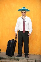 Businessman wearing sunglasses and sombrero with suitcase